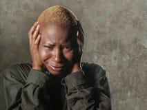 Junge stilvolle traurige und deprimierte afroe-amerikanisch schwarze Frau, die in der Verzweiflung halten Haupt mit den Händen si Stockbilder