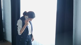 Junge stolze Geschäftsfrau spricht an ihrem Handy mit Kunden, bei der Stellung des nahen Bürofensters stock video
