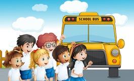 Junge Studenten, die auf das schoolbus warten lizenzfreie abbildung