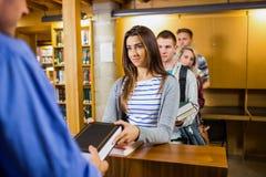 Junge Studenten in Folge am Bibliothekszähler Lizenzfreie Stockfotografie