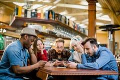 Junge Studenten oder Mitarbeiter, die zusammen Smartphones an der Kaffeestube, verschiedene Gruppe verwenden Zuf?lliges Gesch?ft, stockbild