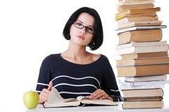 Junge Studentenfrau, die am Schreibtisch studiert Lizenzfreies Stockfoto