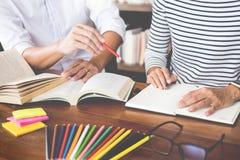Junge Studentenmitschüler helfen aufholendem Arbeitsbuch des Freunds und Lernen- Privatunterricht in einer Bibliothek, in einer A stockfoto