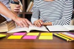Junge Studentenmitschüler helfen aufholendem Arbeitsbuch des Freunds und Lernen- Privatunterricht in einer Bibliothek, in einer A lizenzfreie stockfotografie
