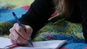 Junge Studentin des Sed liegt auf einem Bett und schreibt in ihr Tagebuch jugendliche Erfahrungen 4K stock video