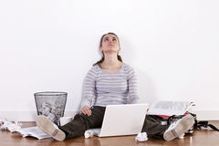 Junge Studentin, die auf dem Boden umgeben durch Bücher und Unordnung sitzt stockbild