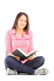 Junge Studentin, die auf einem Boden sitzt und ein Buch hält Lizenzfreies Stockbild