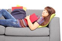 Junge Studentin, die auf einem Sofa mit Buch schläft Lizenzfreie Stockfotografie