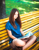 Junge Studentin, die auf gelber Bank sitzt Stockfotografie