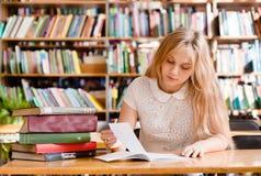 Junge Studentin, die Aufgaben in der Bibliothek tut Stockfotografie