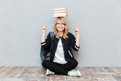 Junge Studentin, die Bücher auf Kopf und dem Zeigen hält Stockfotografie