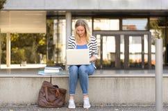 Junge Studentin, die draußen unter Verwendung des Laptops sitzt Lizenzfreie Stockbilder