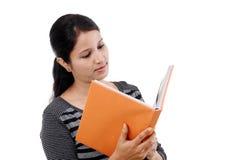 Junge Studentin, die ein Lehrbuch liest Stockbilder