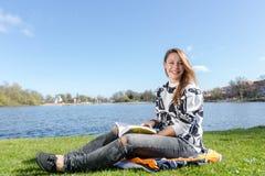 Junge Studentin, die in einem Park sitzt und ein Buch liest Stockfotografie