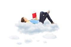 Junge Studentin, die einen Roman liest und auf Wolken liegt Lizenzfreies Stockfoto