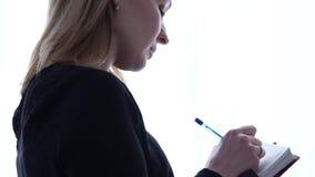 Junge Studentin schreibt in ihr Tagebuch, das nahe dem Fenster steht jugendliche Erfahrungen 4K stock video
