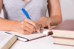 Junge Studentin schreibt in Notizbuch mit blauem Stift und in vollen Schreibtisch mit Buch lizenzfreie stockfotos