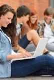 Junge studierende Frau, die Laptop außerhalb des Colleges verwendet Stockfotos