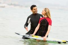 Junge Surferfamilientaille tief im Wasser Stockbilder