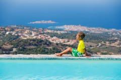 Junge am Swimmingpool Stockfotos