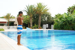 Junge am Swimmingpool Stockfoto