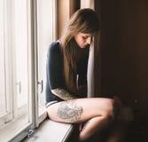 Junge tätowierte Frau, die auf dem Fensterbrett sitzt Stockbilder