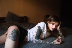 Junge tätowierte Frau, die in Bett legt Stockbilder