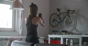 Junge tätowierten die Frau, die Smartphone für die Spurhaltung während des Haupteignungssporttrainings verwendet Inländisches Tra stock footage