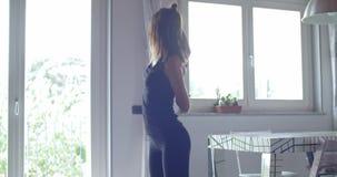 Junge tätowierten die Frau, die vor Eignungssporttraining zu Hause ausdehnen tuend aufwärmt Inländisches Training des Wohnzimmers stock video footage