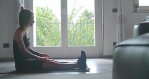 Junge tätowierten die Frau, die vor Eignungssporttraining zu Hause ausdehnen tuend aufwärmt Inländisches Training des Wohnzimmers stock video