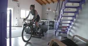 Junge tätowierten die Radfahrerfrau, die zu Hause mit Eignungs-Sporttraining des Fahrrades radfährt Inländisches Training des Woh stock video footage