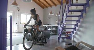 Junge tätowierten die Radfahrerfrau, die zu Hause mit Eignungs-Sporttraining des Fahrrades radfährt Inländisches Training des Woh stock video