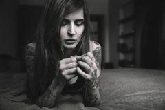 Junge tätowierten Frau mit dem langen Haar, das auf dem Bett liegt und schauten O Stockbilder