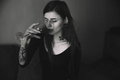 Junge tätowierten Frau mit trinkendem Wein des langen Haares Lizenzfreies Stockbild