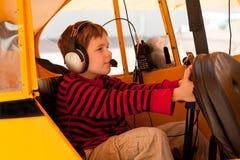 Junge täuscht vor, Pfeifercub-Flugzeug zu fliegen lizenzfreie stockbilder