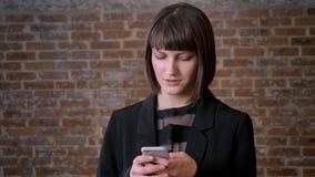 Junge am Telefon plaudernde und lachende Schönheit, stehende nahe Backsteinmauer, bezaubernde Frau mit kurzem Haarschnitt stock video