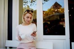 Junge Textnachricht der hübschen Frau Lesean ihrem Zelltelefon, beim Sitzen im bequemen Straßencafé, Lizenzfreie Stockbilder