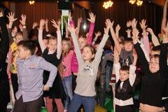 Junge Theaterbesucher Kinder, die enthusiastisch Puppenspieltheater Smeshariki der Kinder Weihnachtsaufpassen Lizenzfreie Stockfotos