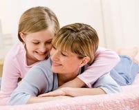 Junge Tochter, die Mutter beim Lügen auf Bett umarmt Lizenzfreie Stockbilder