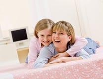 Junge Tochter, die Mutter beim Lügen auf Bett umarmt Stockfotografie