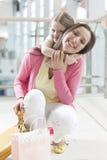 Junge Tochter umarmt Mutter im Einkaufszentrum Stockfotografie