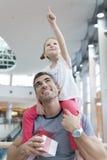 Junge Tochter zeigt und sitzt auf Vaterschultern Stockfoto