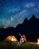 Junge Touristen Mann und Frau, die den sternenklaren Himmel des Glanzes nachts betrachten Glückliches Paar, das nahe Zelt und Lag lizenzfreies stockbild