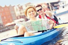 Junge Touristen mit einer Karte in einem Kanu Stockbild