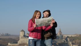 Junge Touristen, welche die lokale Karte auf dem alten Straßenhintergrund, nach neuem Bestimmungsort suchend grasen draußen stock video