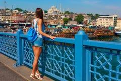 Junge touristische Frau auf Galata-Brücke, goldene Hornbucht, Istanbul Panoramastadtbild von berühmter touristischer Bestimmungso lizenzfreies stockbild