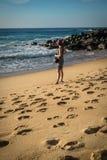 Junge touristische Frau, die auf dem sandigen Strand des atlantischen Ufers Fotos des schönen Meerblicks und der Surfer machend s Lizenzfreie Stockfotos