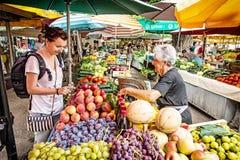 Junge touristische Frau, die frische Frucht von der alten Frau am Markt kauft Stockfoto