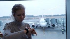 Junge touristische Frau, die nach ihrem Flugstatus auf dem Zeitplanbrett sucht und Zeit auf intelligenten Uhren im Flughafen über stock footage