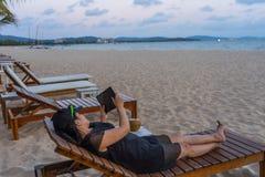 Junge touristische Gebrauchstablette auf dem Strand lizenzfreie stockfotos